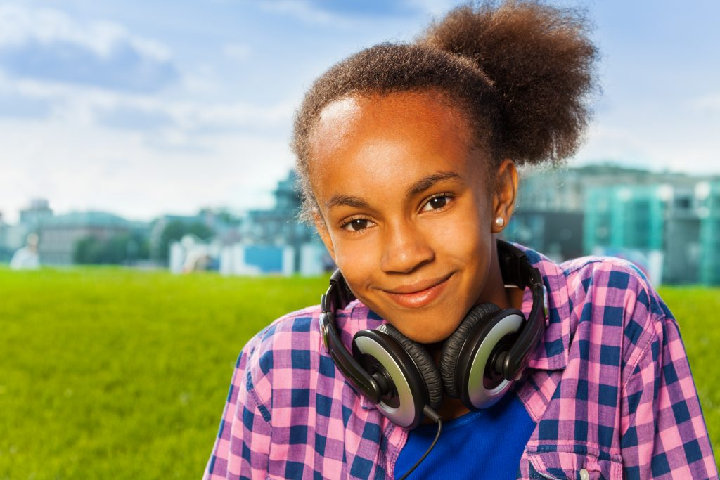 girl sitting on green grass in summer during day wearing headphones
